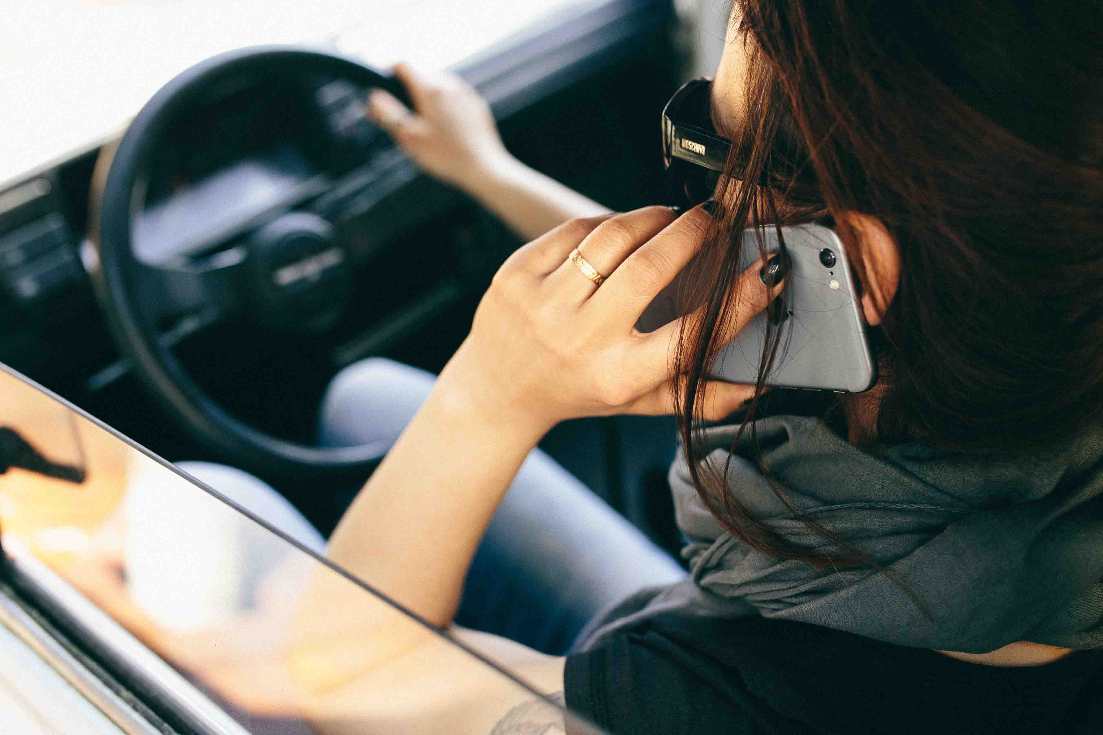kaboompics-com_woman-talking-on-a-mobile-phone-while-driving-car